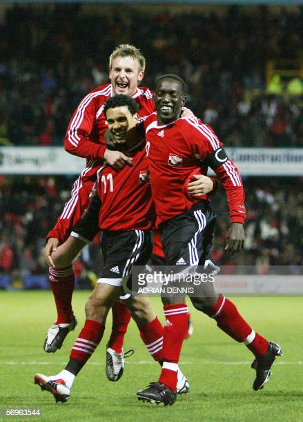 London, UNITED KINGDOM: Trinidad and Tobago players Chris Birchall Carlos Edwards celebrate with Dwight Yorke after he scored the opening goal...