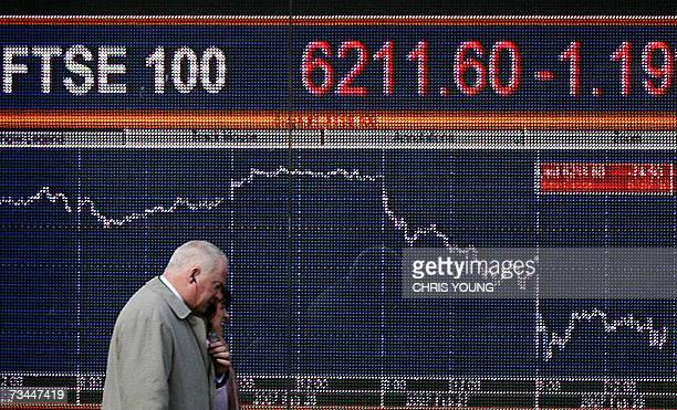 Unidentified business people walk past a financial information board in west London 28 February 2007 Europe's main stock markets extended heavy...