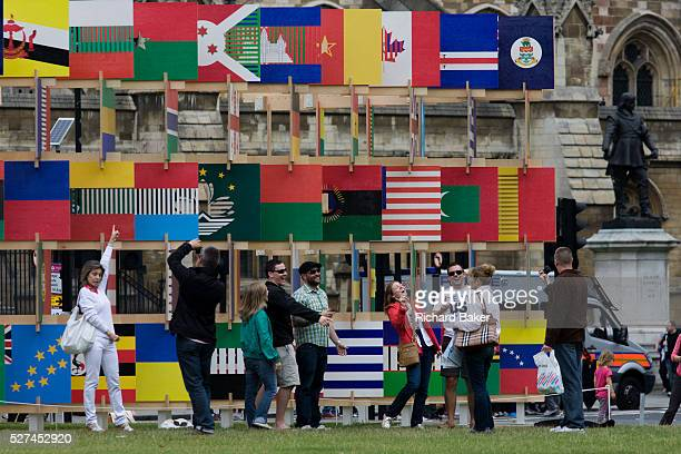 London visitors for the 2012 Olympics admire the 'House of Flags' a structure of 206 panels containing the flag icons of all the countries...