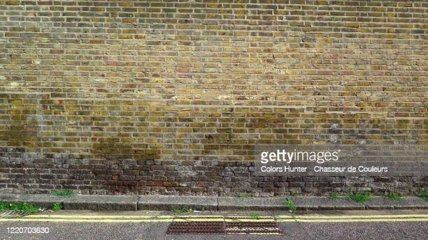 london weathered brick wall with asphalt street and yellow lines - street style stock pictures, royalty-free photos & images