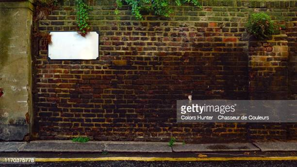 london weathered brick wall with ivy and road - road sign stock pictures, royalty-free photos & images