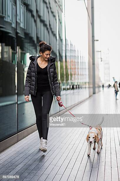 UK, London, woman and her dog walking on pavement in the city