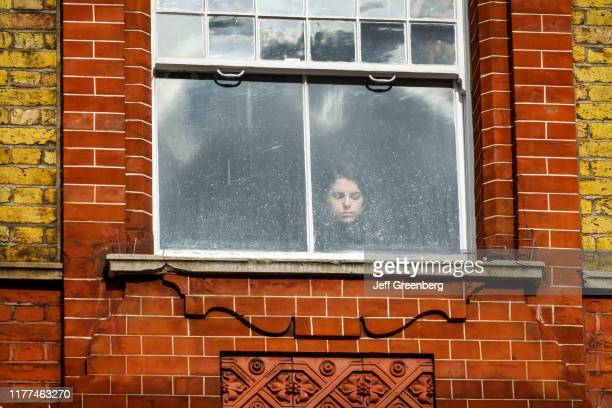 London woman looking through window with eyes closed