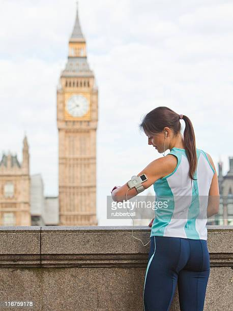 UK, London, Woman with mp3 player in front of Big Ben