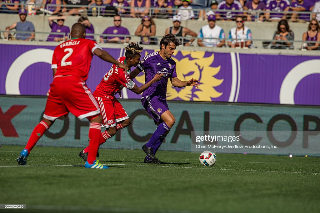 London Woodberry #28 of the New England Revolution grabs Kaka #10 of the Orlando City Lions at the Citrus Bowl in Orlando, Florida on April 17, 2016.