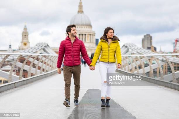 uk, london, young couple walking hand in hand on bridge in front of st pauls cathedral - padded jacket stock pictures, royalty-free photos & images