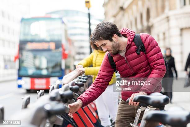 uk, london, young man renting bicycle from bike share stand in city - bending over stock pictures, royalty-free photos & images
