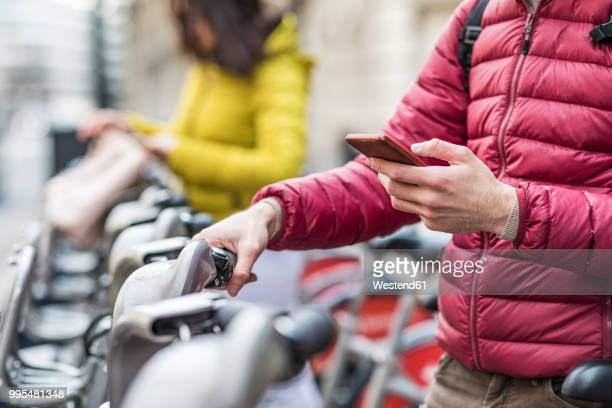 UK, London, young man renting bicycle from bike share stand in city, close-up