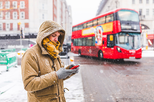 UK, London, young man standing next to the road in the city looking at cell phone - gettyimageskorea