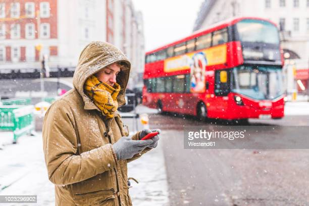 uk, london, young man standing next to the road in the city looking at cell phone - winter weather stock photos and pictures