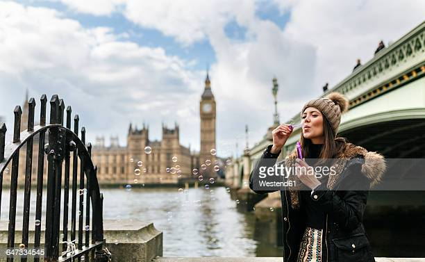 UK, London, young woman blowing soap bubbles