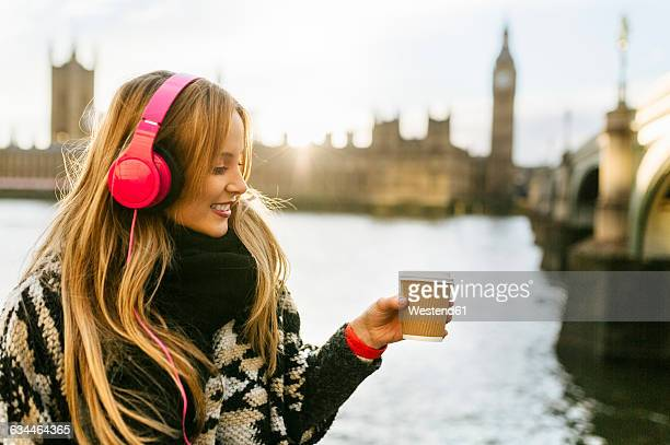 UK, London, young woman listening music and drinking coffee near Westminster Bridge