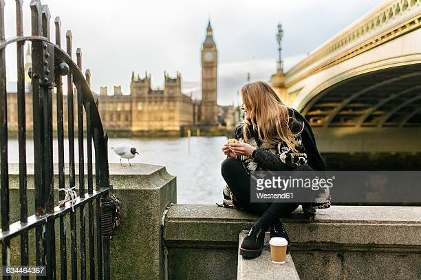 UK, London, young woman taking a snack near Westminster Bridge
