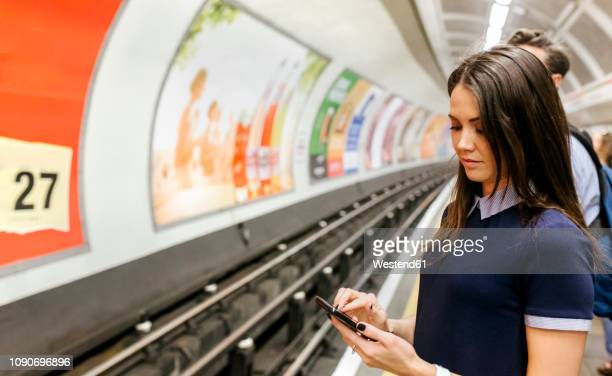 uk, london, young woman waiting at underground station platform looking at cell phone - vertical red tube fotografías e imágenes de stock