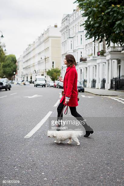UK, London, young woman wearing red jacket crossing the street with her dog