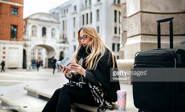 UK, London, young woman with book and luggage on stairs
