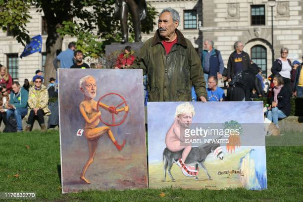 Londonbased satirical artist Kaya Mar holds two of his latest political works outside the Houses of Parliament in central London on October 19 2019...