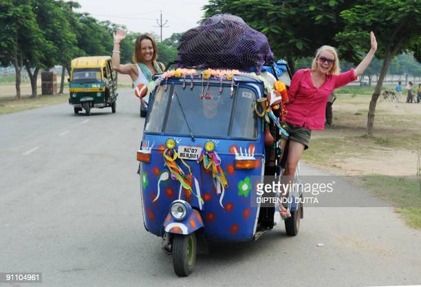 Londonbased 'Some Like It Hot' team member John Tilly drives as teammates Olivia Hague and Katie Ball wave from their rickshaw after joining in aarti...