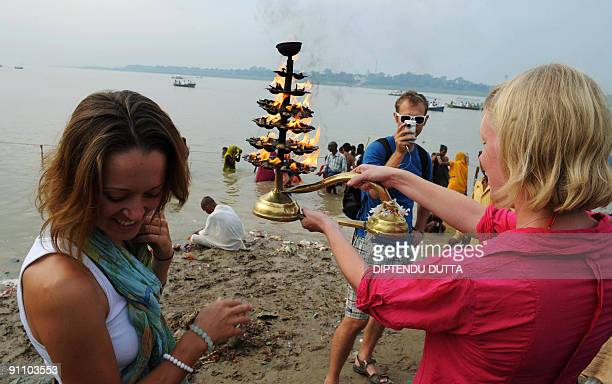 Londonbased 'Some Like It Hot' team member John Tilly takes a photo as teammates Olivia Hague and Katie Ball join in aarti morning prayers on the...
