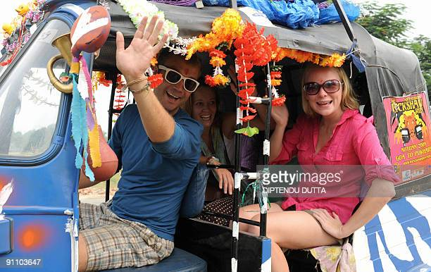 Londonbased 'Some Like It Hot' team members John Tilly Katie Ball and Olivia Hague pose for a photo in their rickshaw after joining in aarti morning...