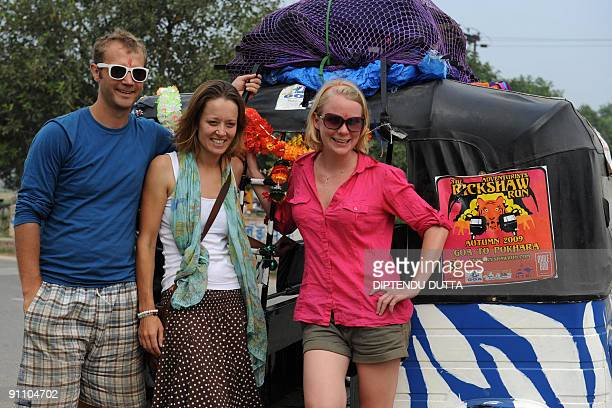 Londonbased 'Some Like It Hot' team members John Tilly Olivia Hague and Katie Ball pose for a photo by their rickshaw after joining in aarti morning...