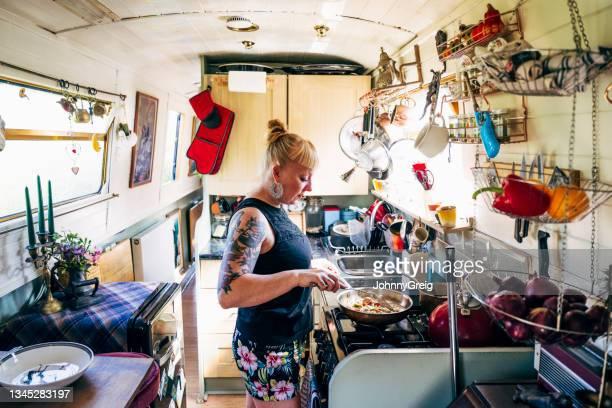 londoner enjoying alternative lifestyle on narrowboat - ambient light stock pictures, royalty-free photos & images