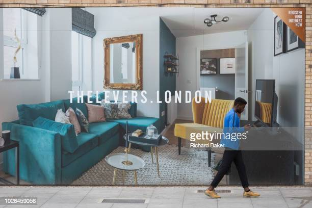 A Londoner walks past a marketing billboard for The Levers a new apartment development on the Walworth Road at Elephant And castle on 4th September...