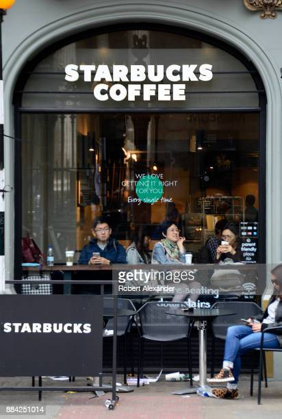 Londoners and tourists enjoy a stop at a Starbucks Coffee shop in London England