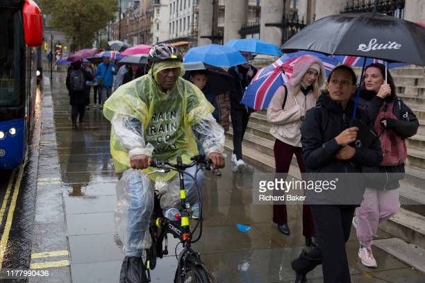 Londoners and visitors to the capital endure heavy rainfall on an autumn afternoon in Trafalgar Square on 24th October 2019 in Westminster London...