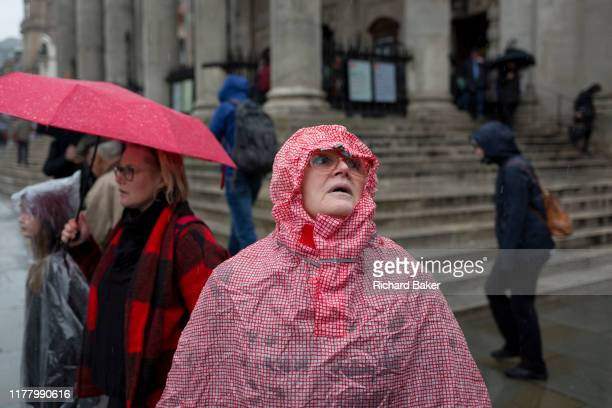 Londoners and visitors to the capital endure heavy rainfall on an autumn afternoon outside St. Martin-in-the-Fields church on Trafalgar Square, on...