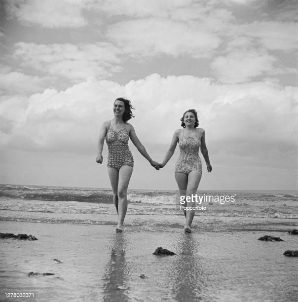 Londoners Audrey Elgar and Muriel Turner walk up the beach after returning from a swim in the sea during their holiday in the Welsh seaside resort of...