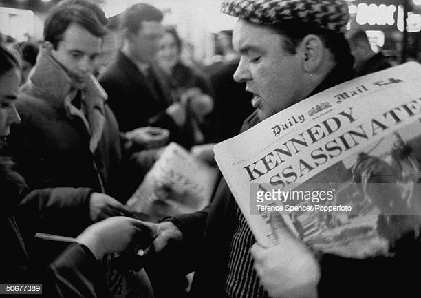 Londoners buying newspapers and reading about details of John F Kennedy's assassination