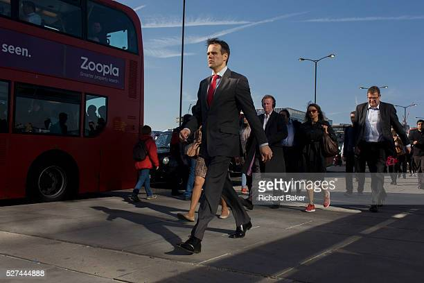 Londoners cross southbound over London Bridge during the evening rush hour A smartlydressed businessman walks briskly along with others commuters...
