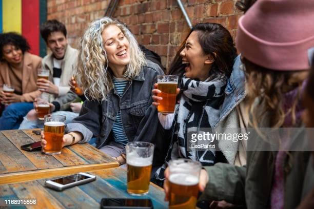 londoners group of friends meet up in a pub - friendship stock pictures, royalty-free photos & images