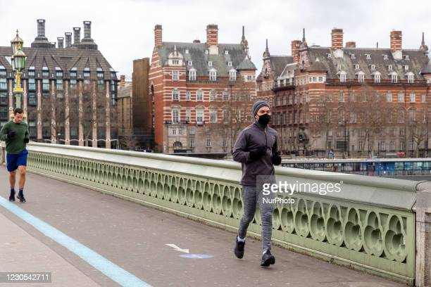 Londoners in protective face masks are seen jogging on Westminster Bridge as the UK's government introduced strict Coronavirus restrictions earlier...