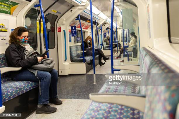 Londoners in protective facemasks are seen commuting in London Tube as the UK's government introduced strict Coronavirus restrictions - tier 4 Stay...