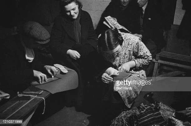 Londoners making slippers in a craft lesson given by London County Council teachers at an air raid shelter in Bermondsey London during the Blitz...