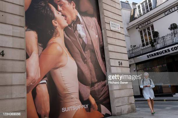 Londoners pass beneath a tall advertising billboard, by menswear retailer Suitsupply, of an intimate kissing couple on Covid 'Freedom Day'. This date...