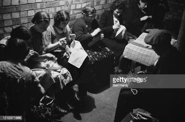 Londoners sewing in a craft lesson given by London County Council teachers at an air raid shelter in Bermondsey London during the Blitz March 1941...