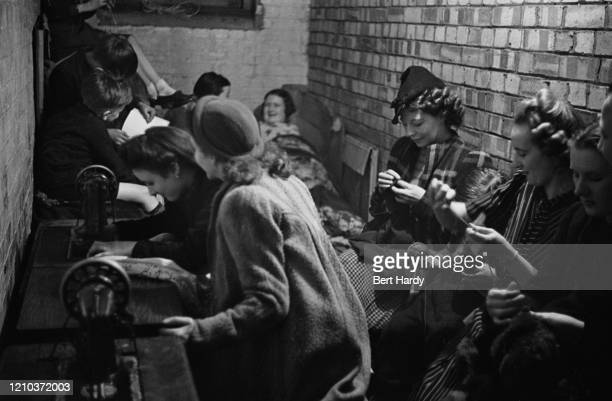 Londoners sewing in a craft lesson given by London County Council teachers at an air raid shelter in Bermondsey, London during the Blitz, March 1941....