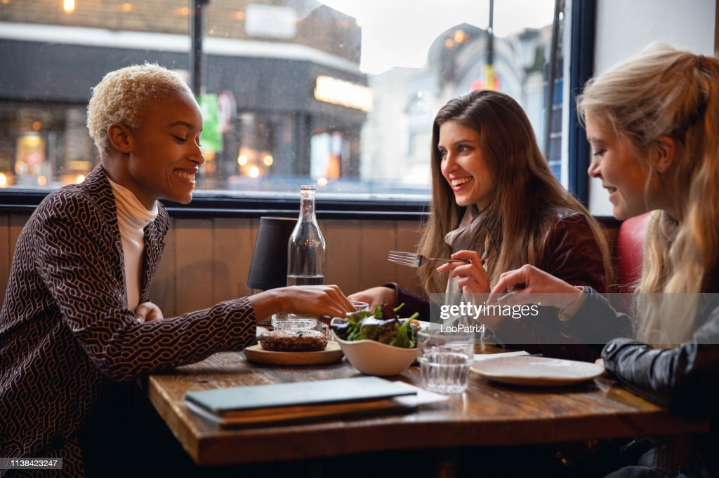 Londoners women eating together at a restaurant : Stock Photo