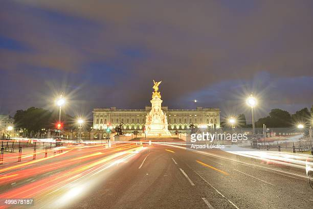 London's Buckingham Palace captured at night with Victoria Memorial in the center. A rising crescent Moon is slightly visible just above the building...