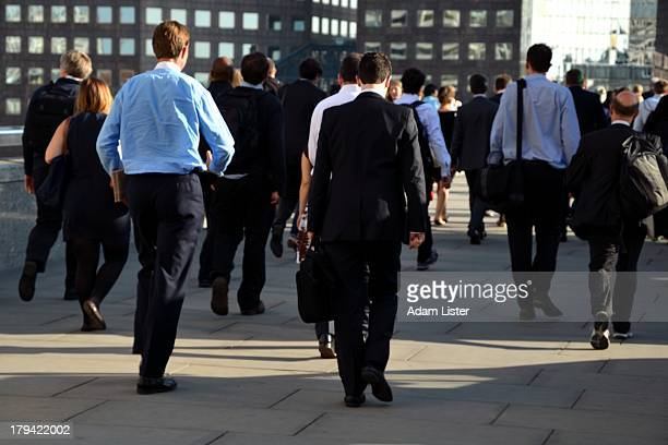 Londons Businessmen, bankers, financiers and City office workers are seen commuting during the daily rush hour on a bright, positive, sunny day. They...