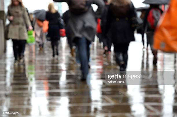 Londons Businessmen, bankers, financiers and City office workers are seen commuting during rush hour in heavy, pouring rain. They mix on the wet...