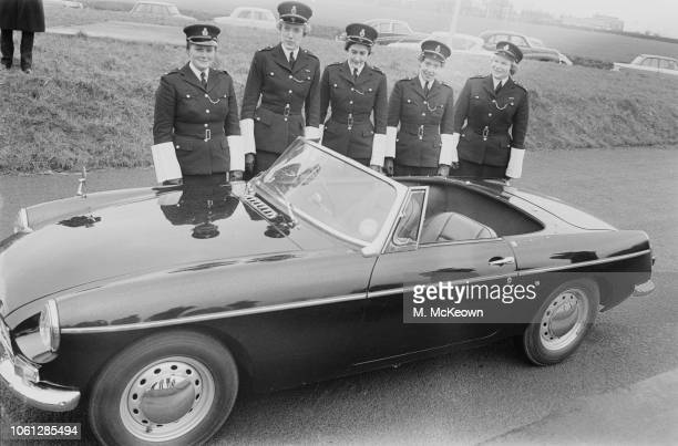 London's first squad of mobile policewomen posed together in uniform behind a British Motor Corporation MGB sports car at a Metropolitan Police press...