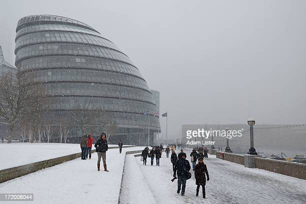 CONTENT] London's iconic City Hall offices of the Mayor of London seen during heavy winter snow fall Avoiding the disruption people are out walking...