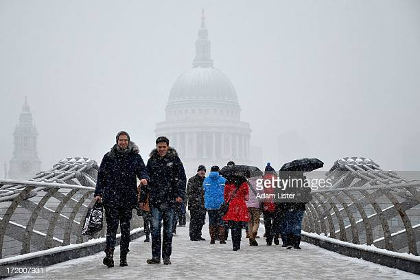 London's iconic St Pauls Cathedral is covered by heavy winter snow fall. People walk across the Millennium Bridge enjoying the festive, seasonal...