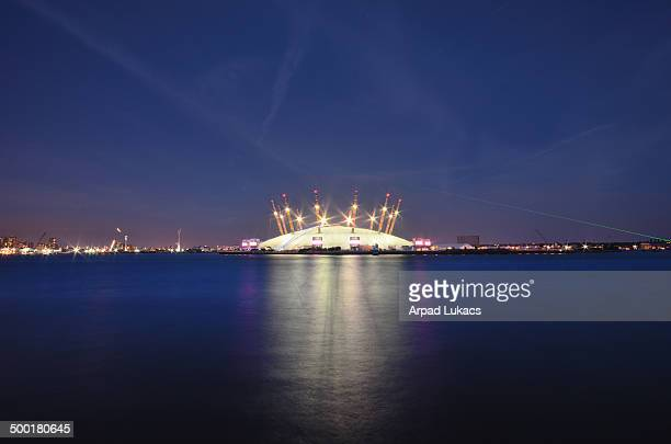 London's Millennium Dome, otherwise known as the O2 Arena captured from London Docklands. The green laser beam on the right comes from Prime meridian...
