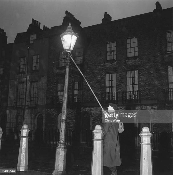 London's oldest lamplighter John Jennings extinguishing a lamp in Clerkenwell at 445 am