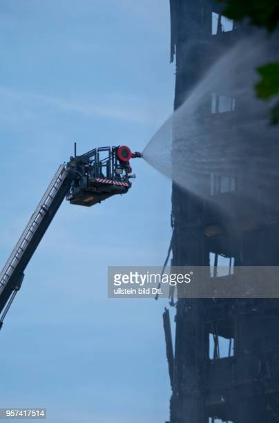 LondonUK 14th June 2017View of fire brigade pouring water on to smouldering remnants of Grenfell Tower in West LondonUK© Julio Etchart/Alamy Live News